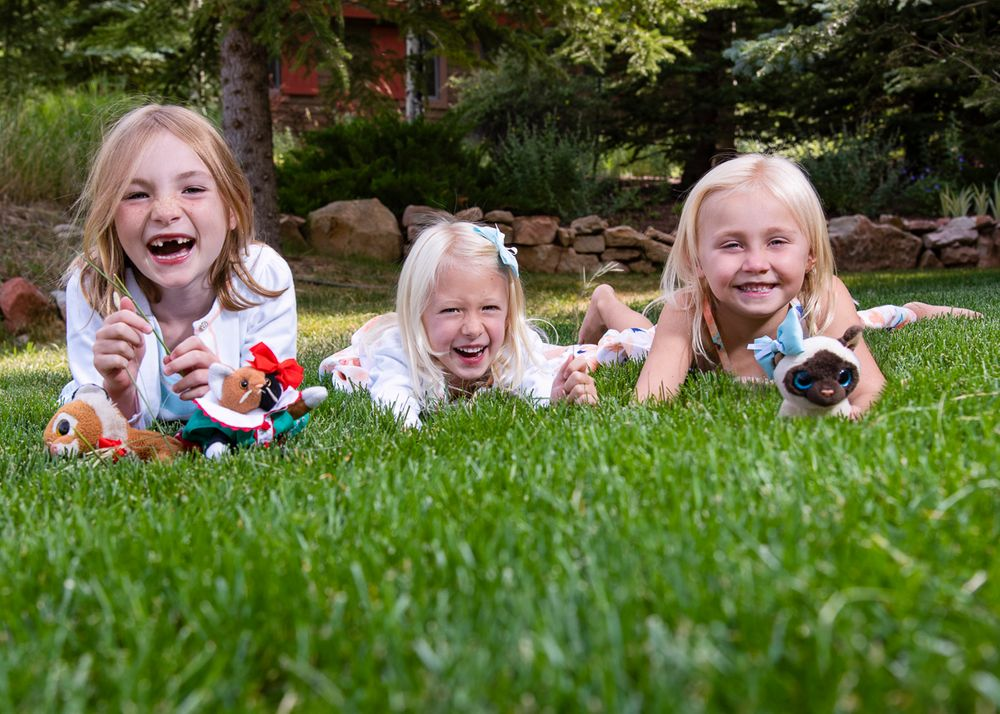 3 little girls laughing, lying in the grass in summer