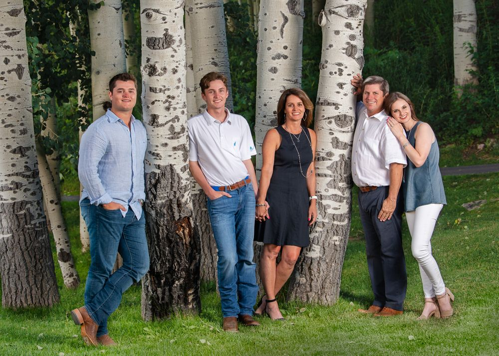 Family with grown children leaning around in the aspen trees in summer