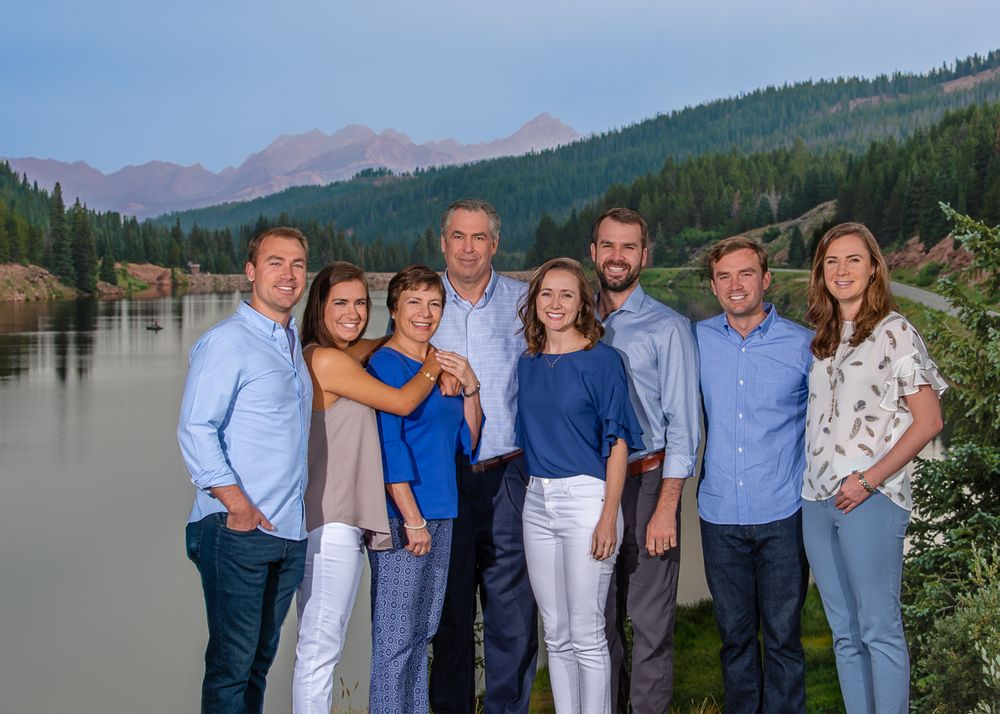 large family portrait with gore range and black lake in the background in summer