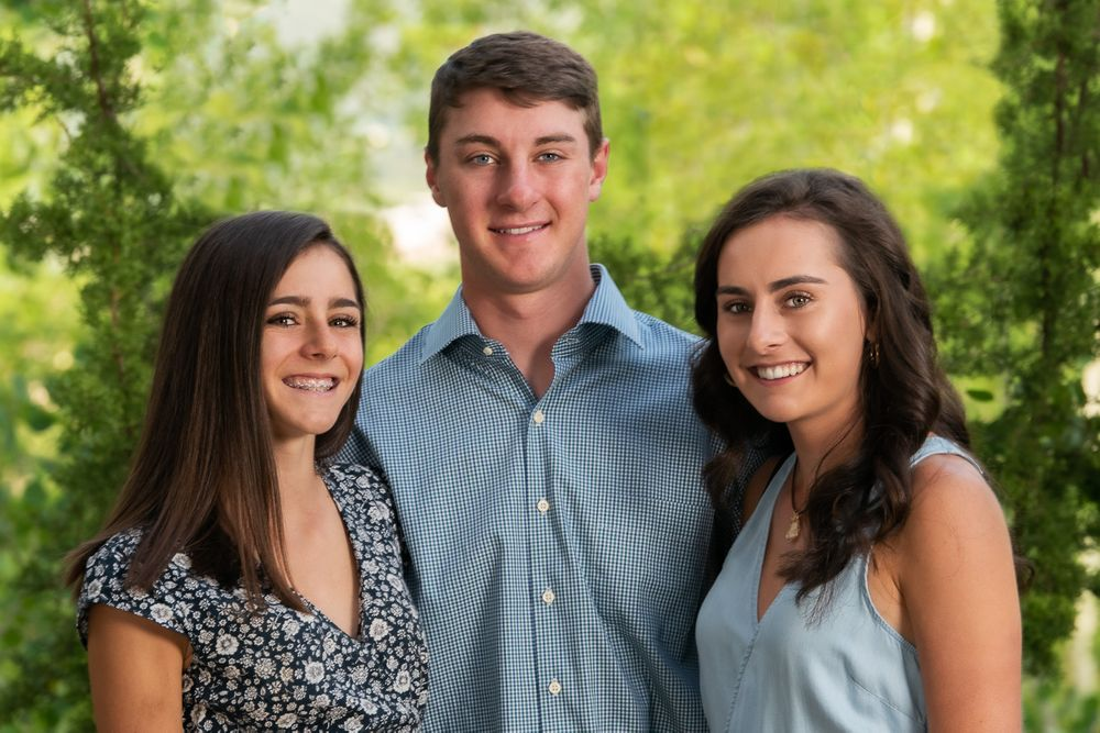 Grown sisters and brother with green summer background