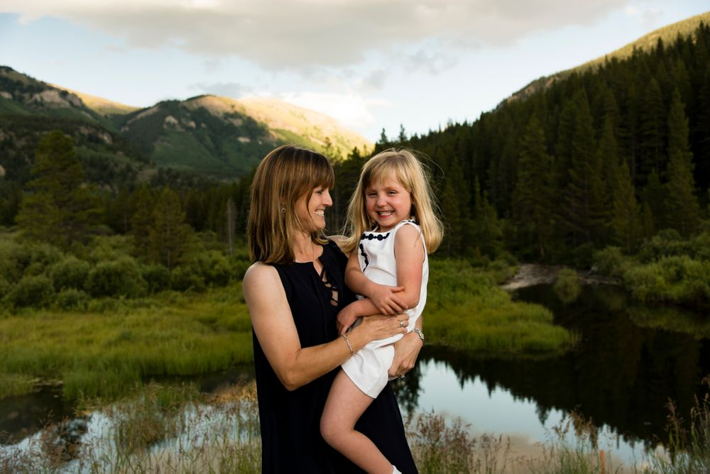 Mom and young daughter with grand mountain views and lake behind them