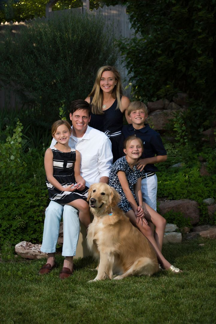 Family of 5 with young kids and a dog with dark green forest background