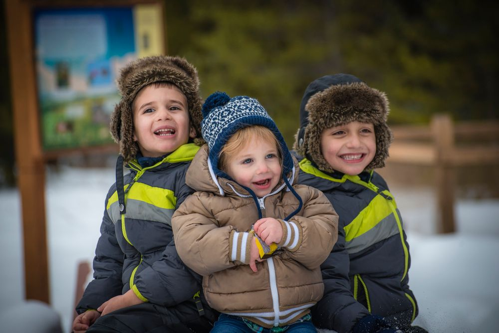 Three little boy siblings in winter clothes in Vail in winter