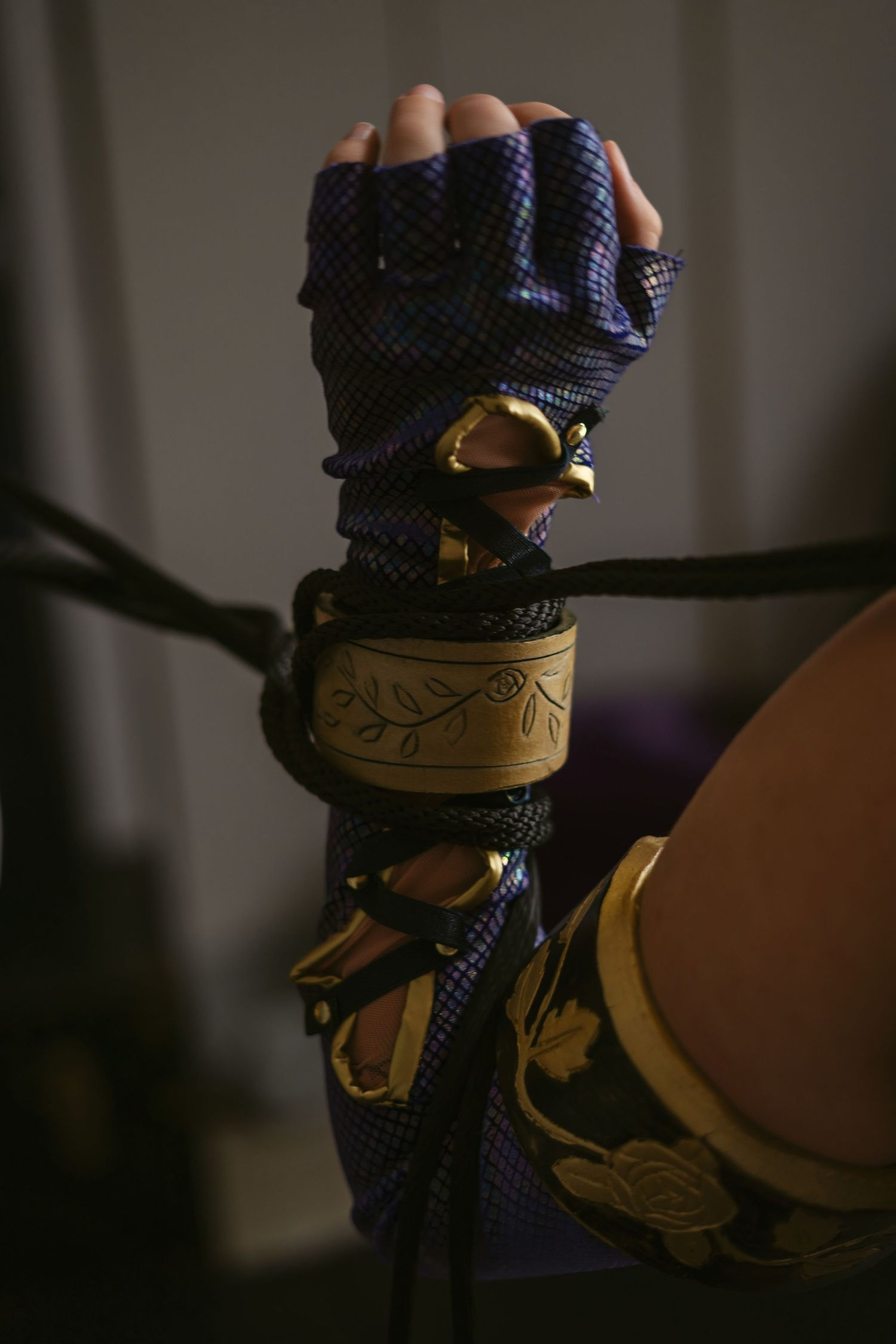 A costumed arm, wearing the glove of Ivy Valentine from Soulcalibur, is bound with ropes pulling in opposite directions