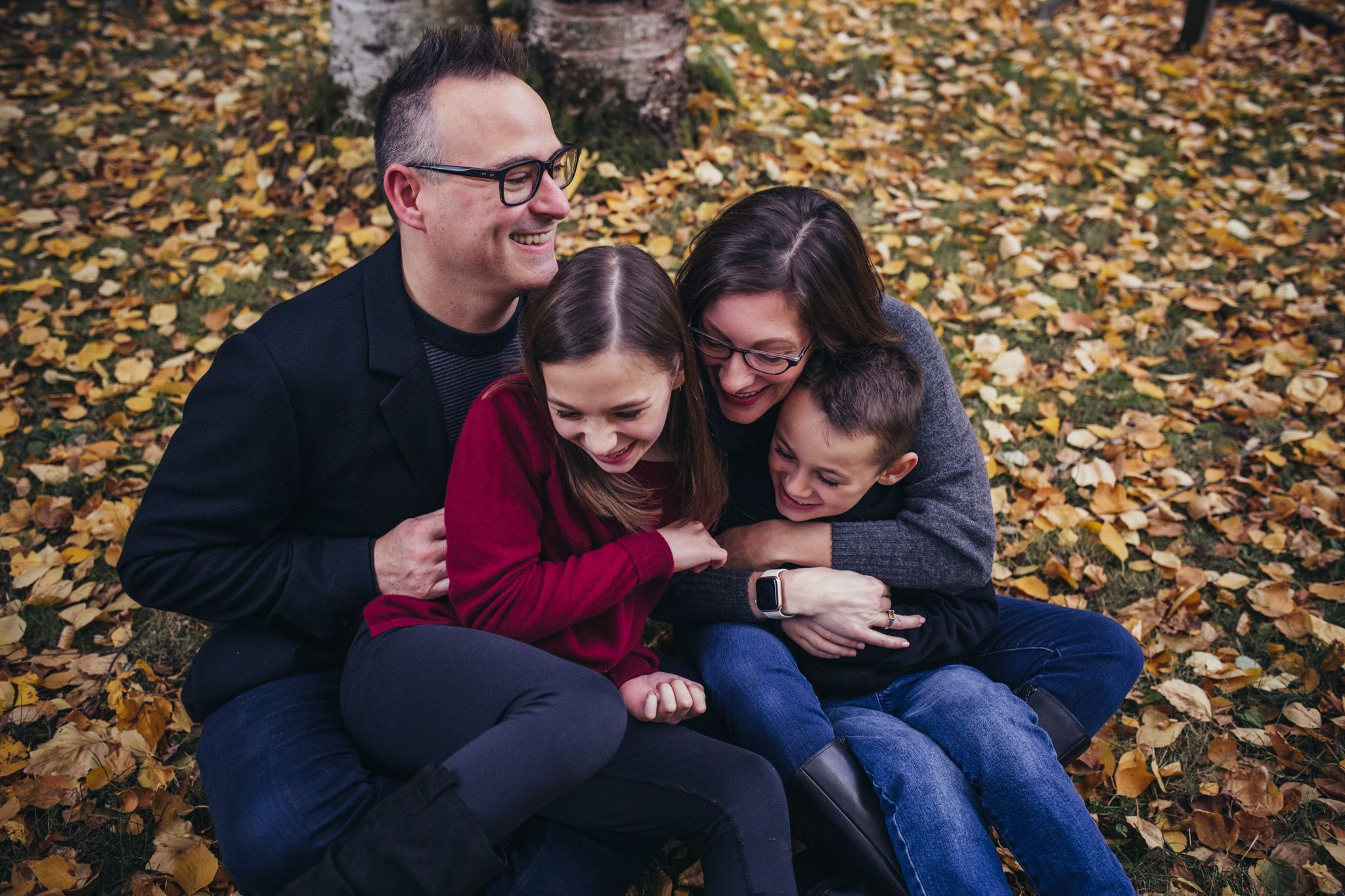 family of four laughing sitting on fall leaves